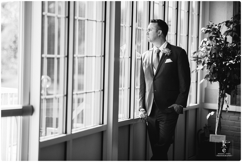 A black and white image of the groom looking out a window at his wedding ceremony.